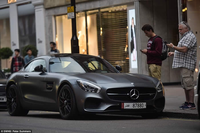 Two passers-by stop to admire one of the supercars, a Mercedes-Benz AMG GT, worth around £110,000,